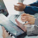 profissionais olhando laptop e tablet com dados relevantes - Auditoria de Conteúdo
