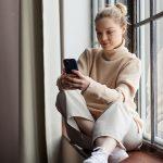 Mulher olhando para o celular - Jornada de Compra para Instituições de Ensino