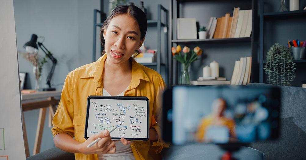 mulher asiática gravando aula pelo celular - iluminação para gravação de videoaulas