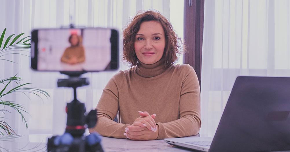 mulher jovem gravando videoaula com celular -plataformas de cursos online EAD