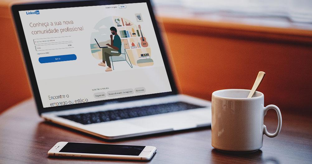 Mesa com laptop, celular e xicara de café - LinkedIn para empresas