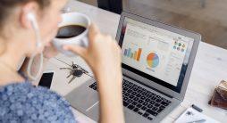 mulher olhando os gráficos no laptop - Mídia paga no marketing digital